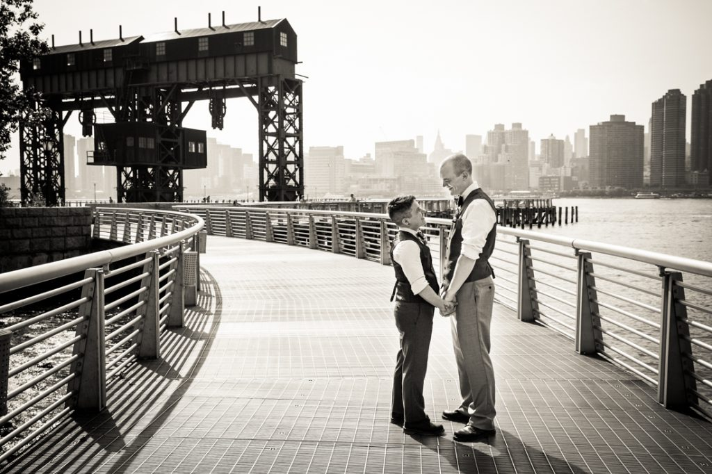Black and white photo of two grooms holding hands at Gantry Plaza State Park