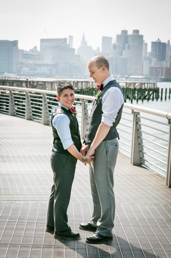 Two grooms holding hands at Gantry Plaza State Park