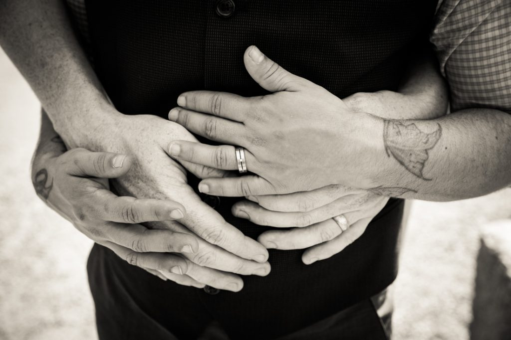 Black and white photo of hands of two grooms