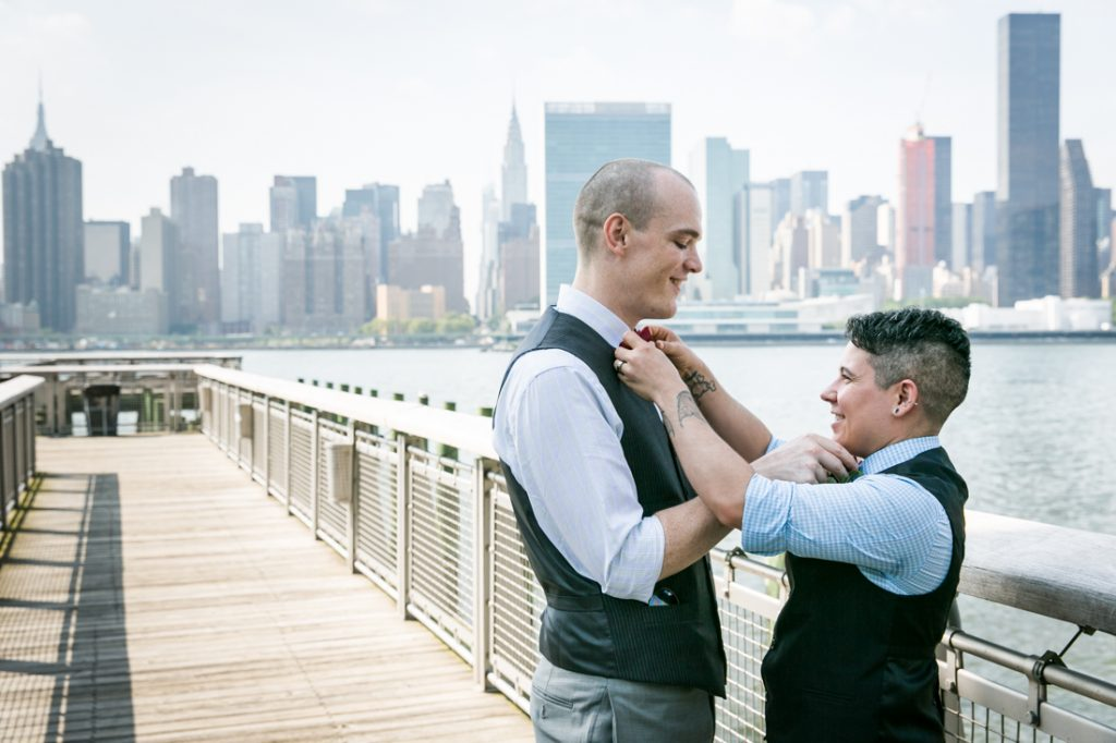 Two grooms adjusting each other's bow ties at Gantry Plaza State Park