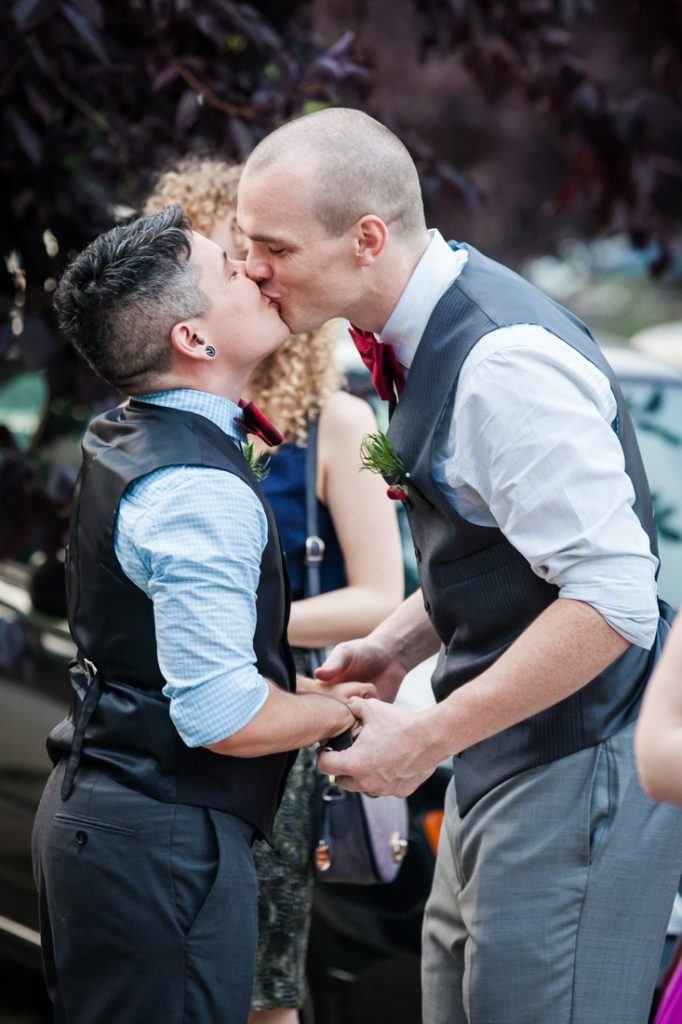 Two grooms kissing outside before at Astoria wedding reception