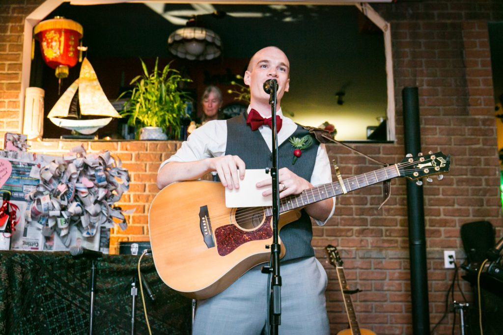 Groom speaking into microphone and holding guitar