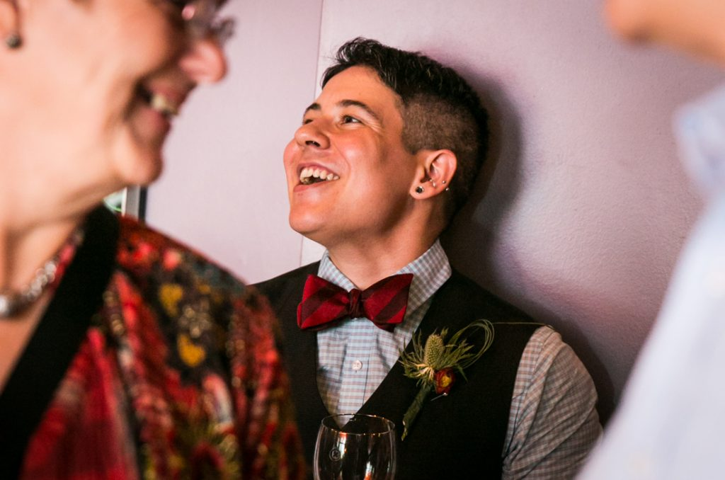 Groom laughing and listening during Astoria wedding reception
