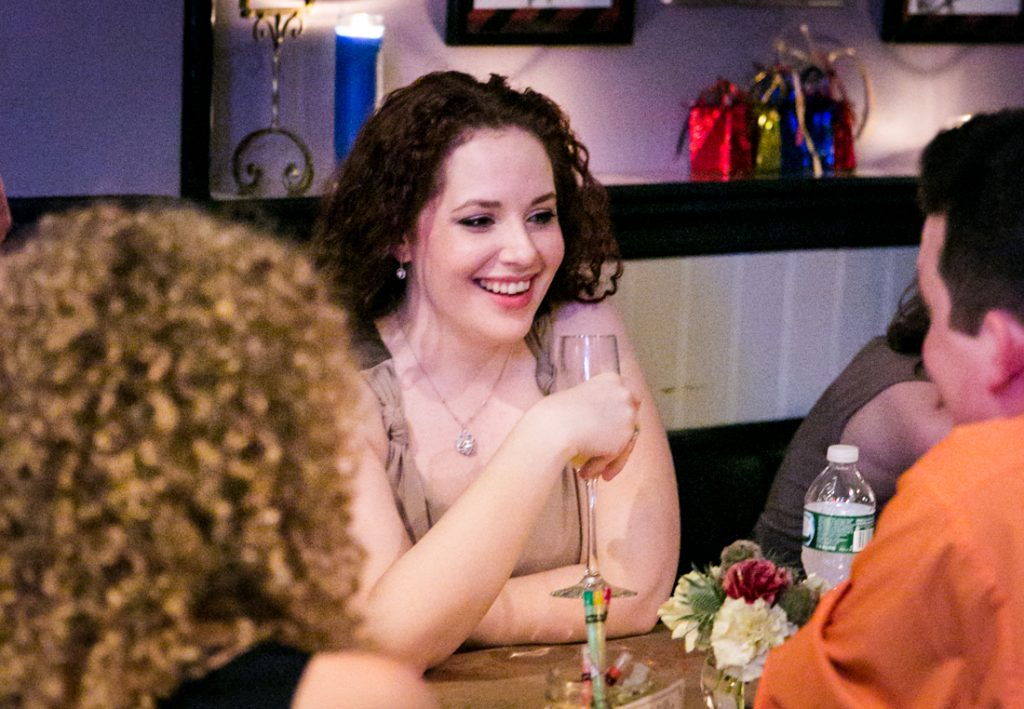 Woman smiling with other guests at Astoria wedding reception