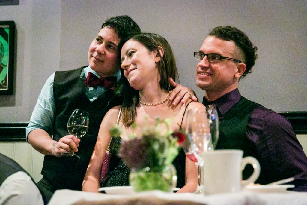 Groom listening with two other guests at Astoria wedding reception