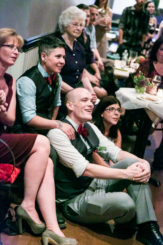 Grooms and guests listening at Astoria wedding reception