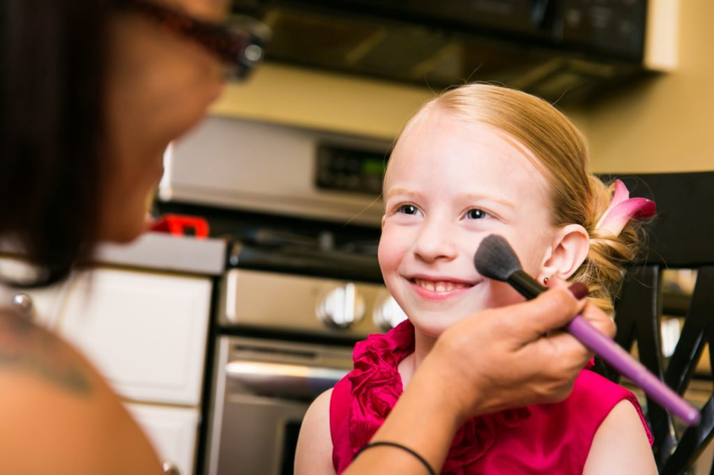 Makeup artist putting blush on little flower girl
