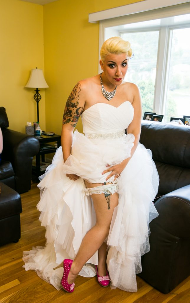 Bride showing off her garter belt and tattoos
