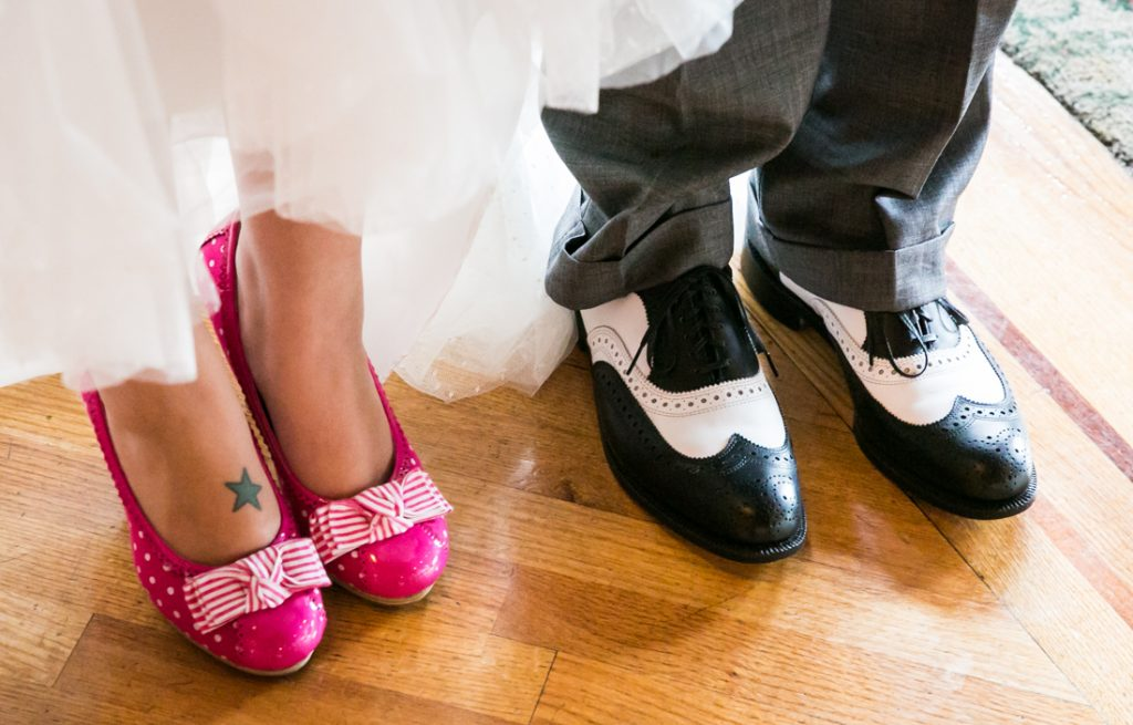 Bride's pink shoes and father of the bride's black and white shoes side by side