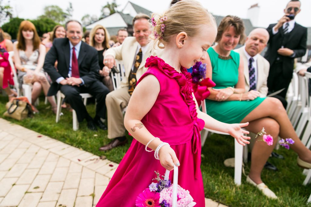Little flower girl in pink dress throwing flowers down aisle at Riviera Waterfront Mansion wedding