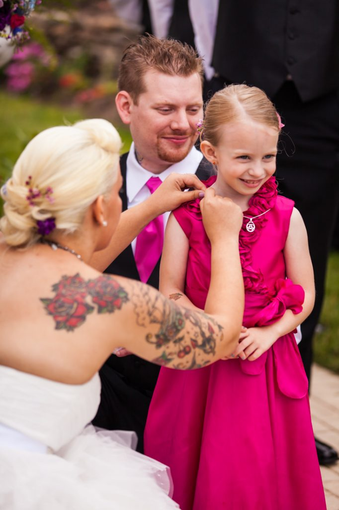 Bride and groom putting necklace on little flower girl at Riviera Waterfront Mansion wedding