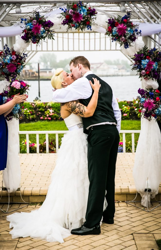 Bride and groom kissing during ceremony at Riviera Waterfront Mansion wedding