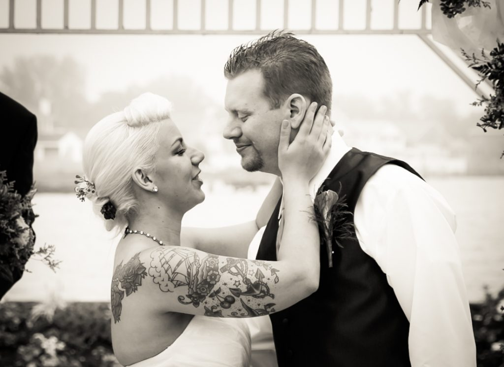 Black and white photo of bride touching groom's face during ceremony