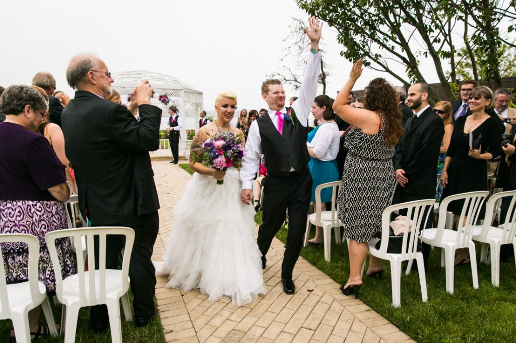 Groom pumping fist while walking with bride down aisle at Riviera Waterfront Mansion wedding