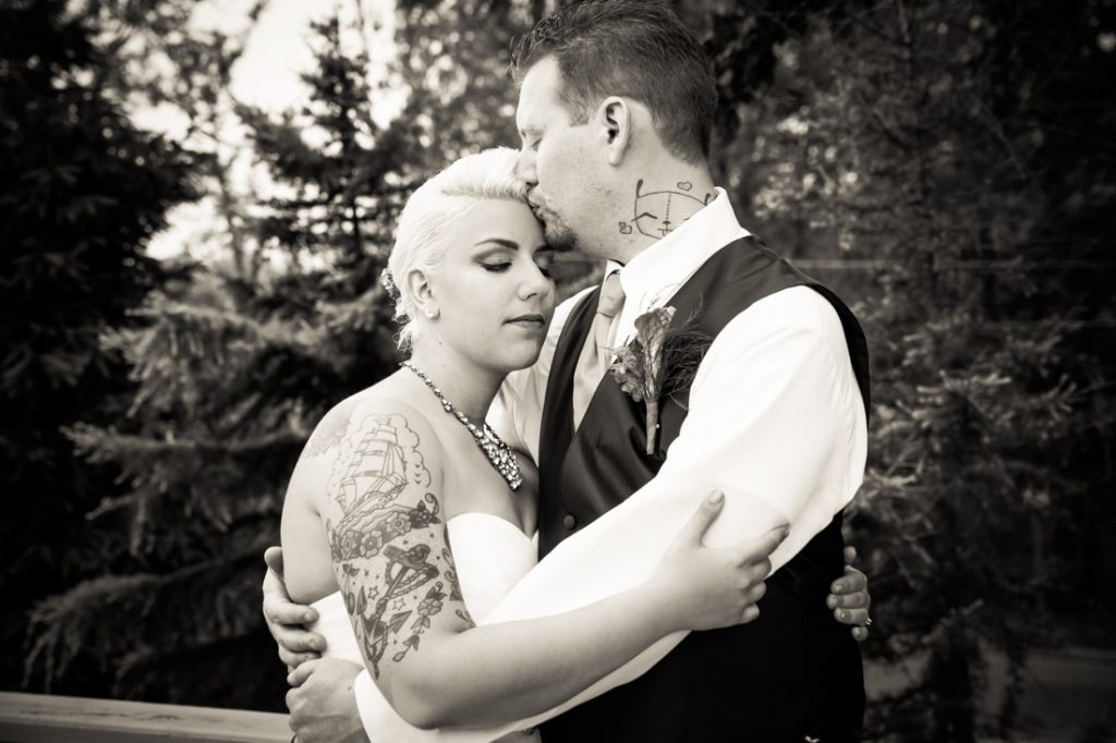 Black and white photo of groom kissing bride on forehead