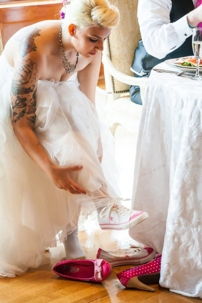 Bride changing shoes into Converse sneakers