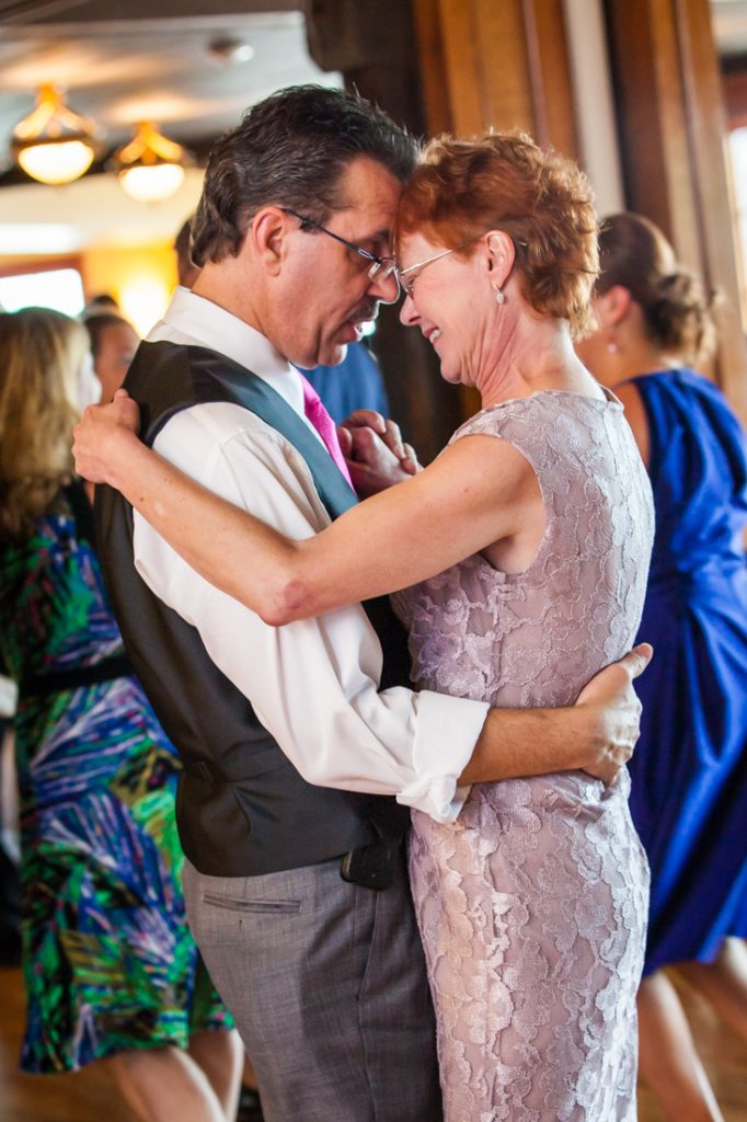 Parents of the bride dancing close during reception