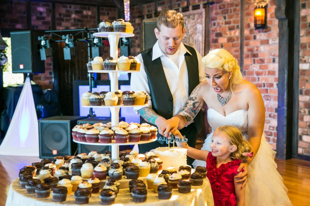 Bride, groom, and flower girl selecting cupcake at Riviera Waterfront Mansion wedding