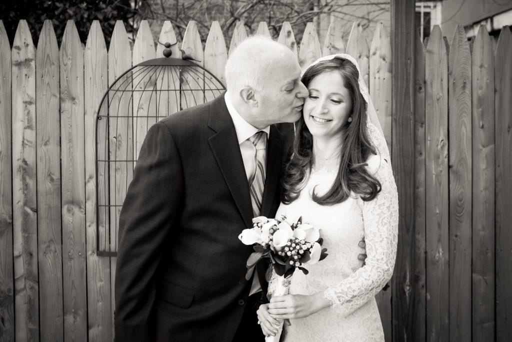 Black and white photo of father kissing bride on side of head