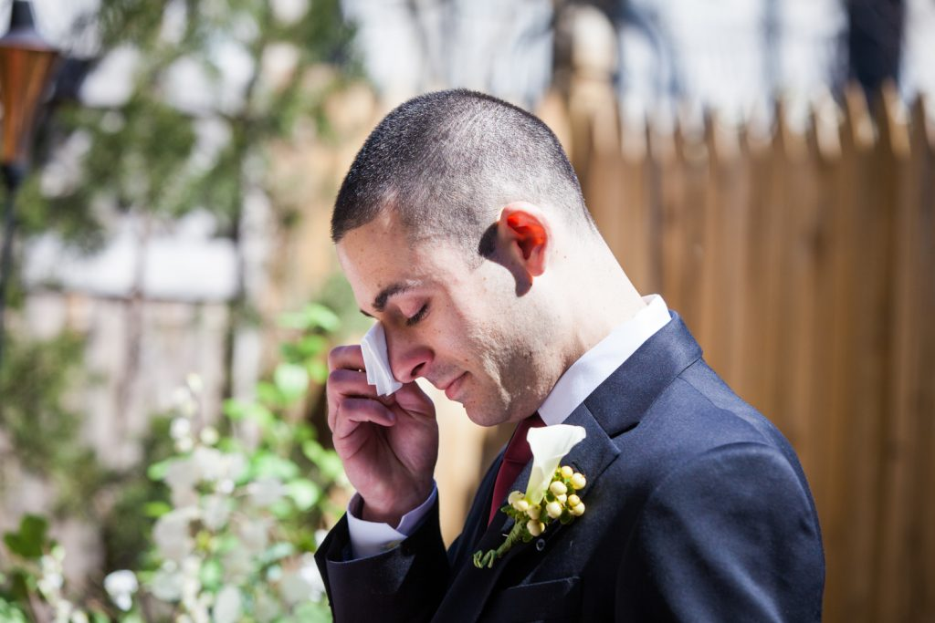 Groom wiping away tear at Brooklyn backyard wedding ceremony