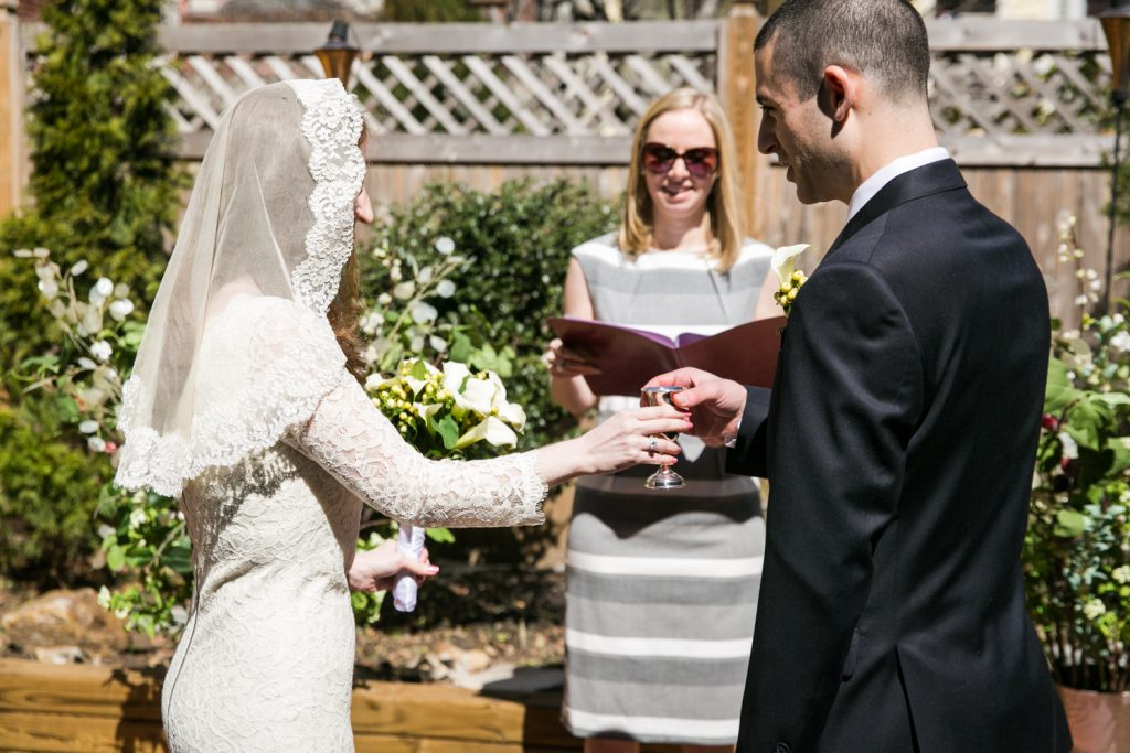 Bride sharing cup of wine with groom at Brooklyn backyard wedding ceremony
