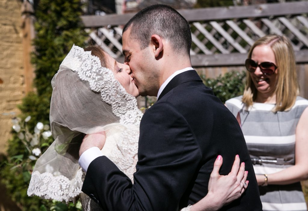 Bride and groom kissing at Brooklyn backyard wedding ceremony