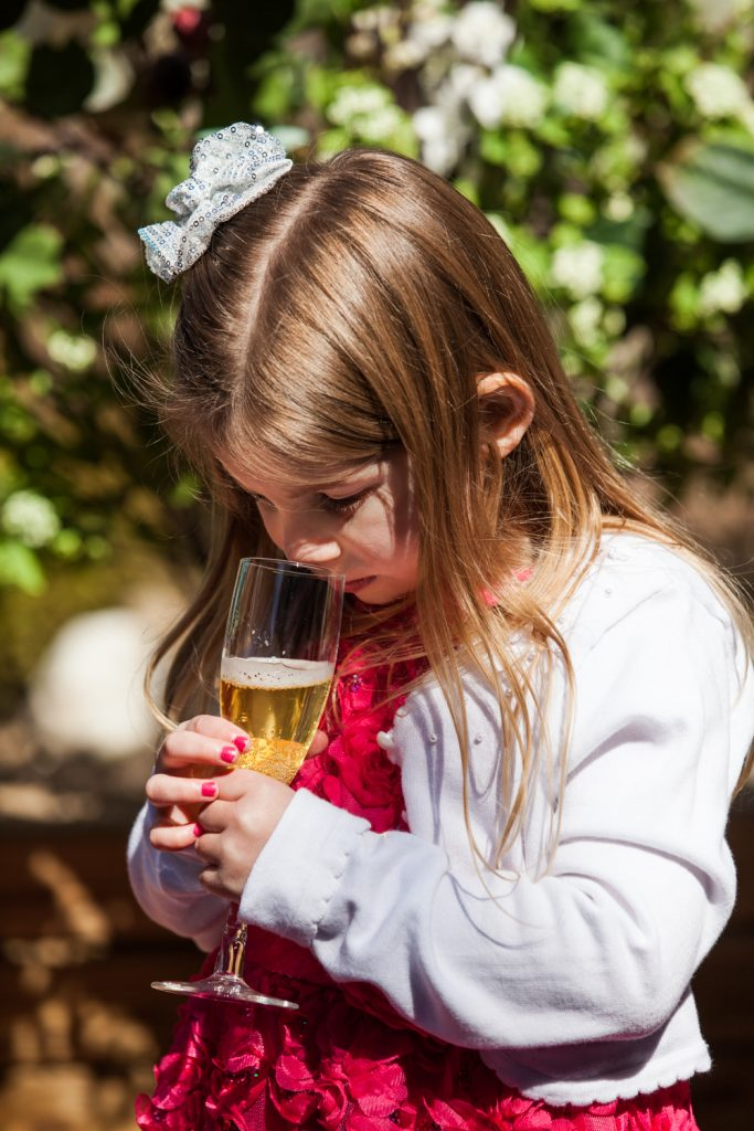 Little girl drinking glass of apple cider in champagne glass