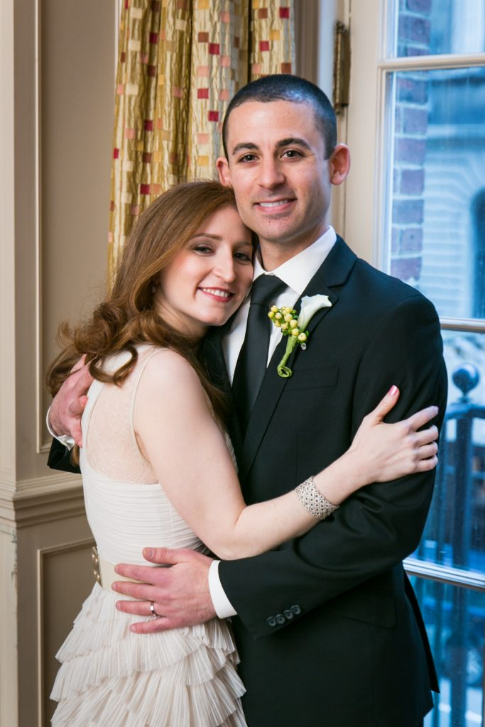 Harvard Club wedding photos of bride and groom hugging in front of window
