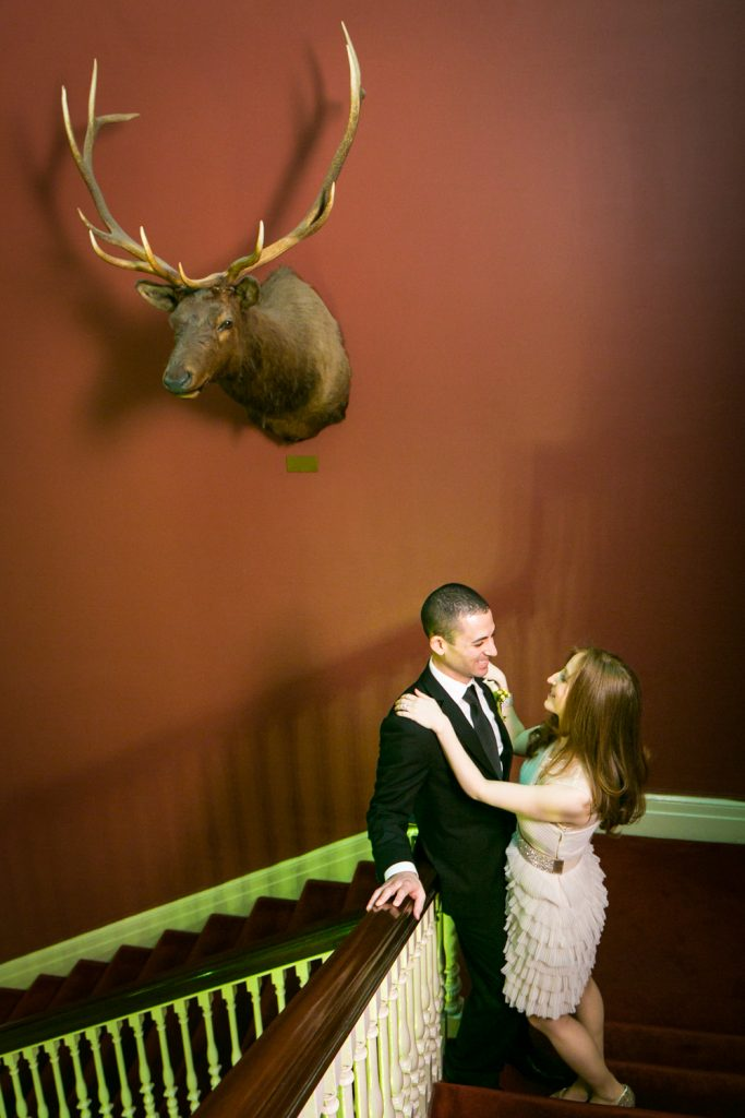 Harvard Club wedding photos of bride and groom on staircase under stuffed moose