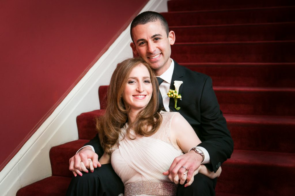 Harvard Club wedding photos of bride and groom sitting on stairs