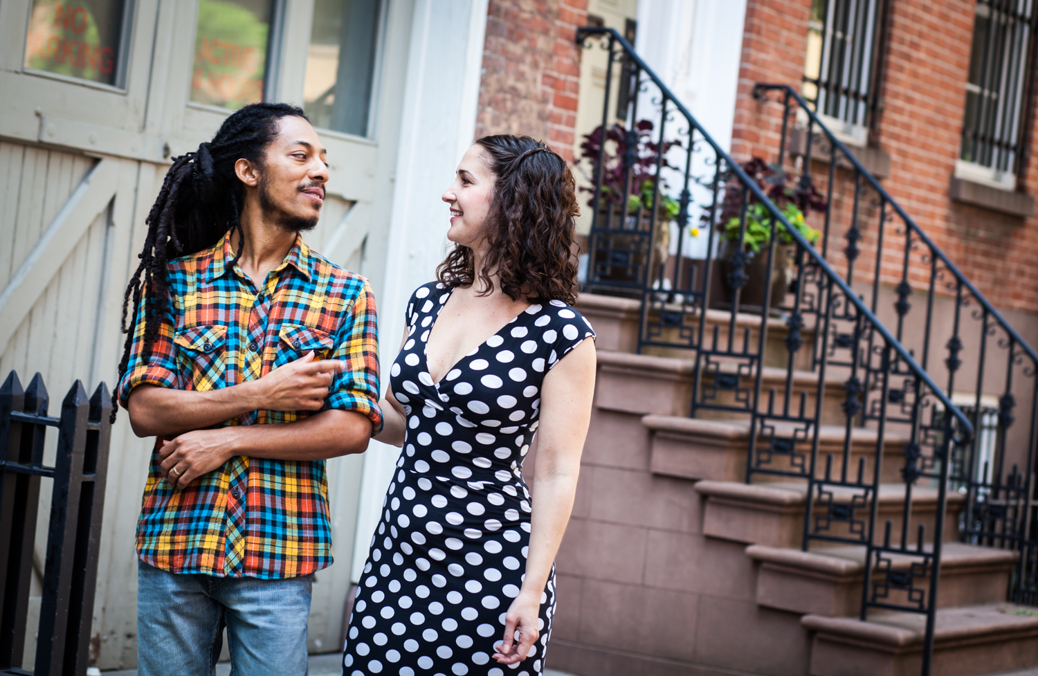 Meatpacking District engagement photos of couple walking past Greenwich Village brownstone