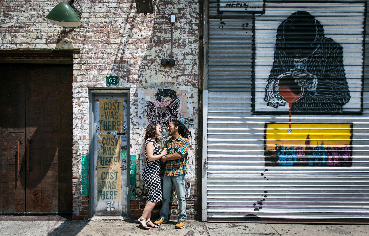 Meatpacking District engagement photos of couple dancing in front of graffiti wall