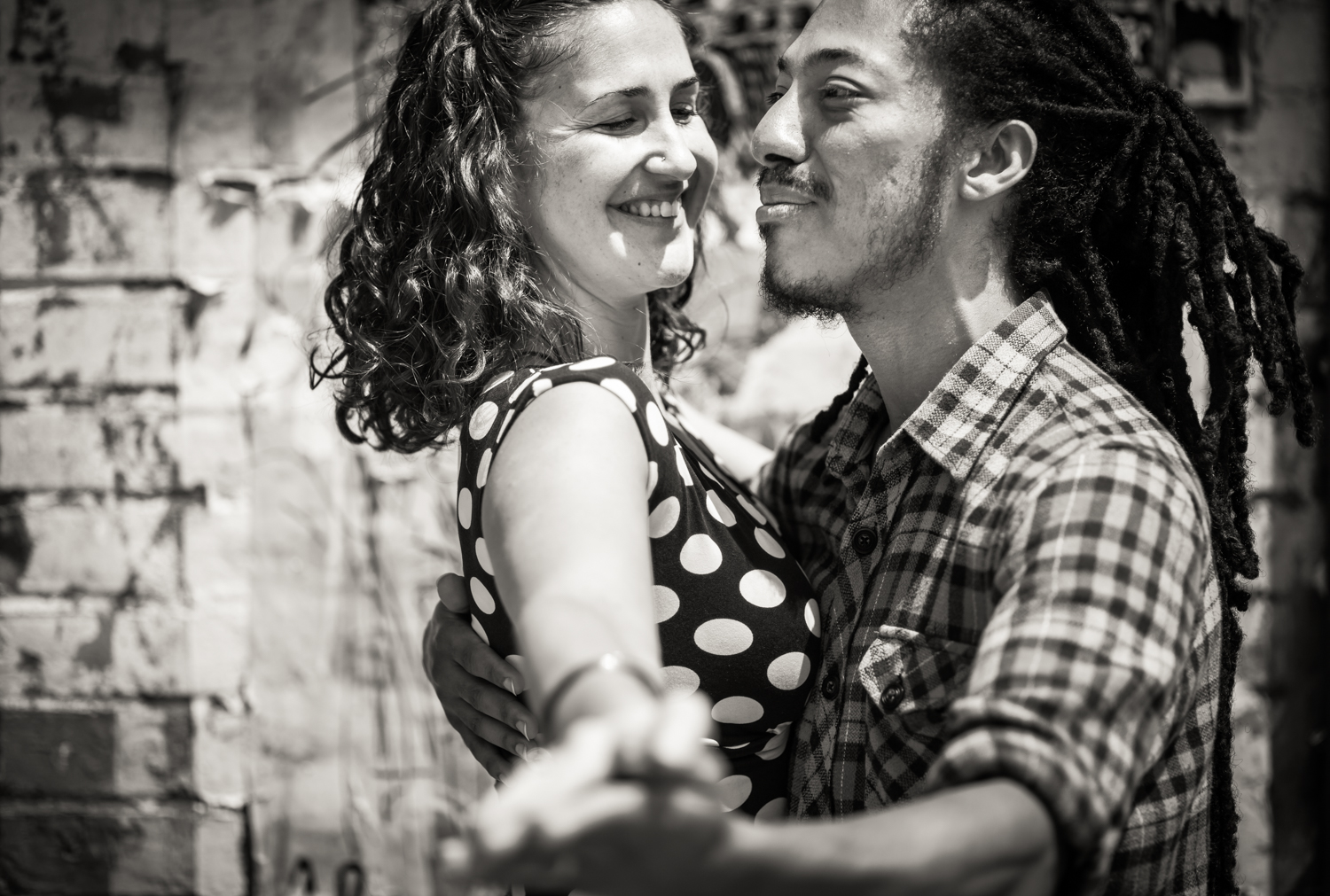 Black and white photo of couple dancing in front of graffiti wall