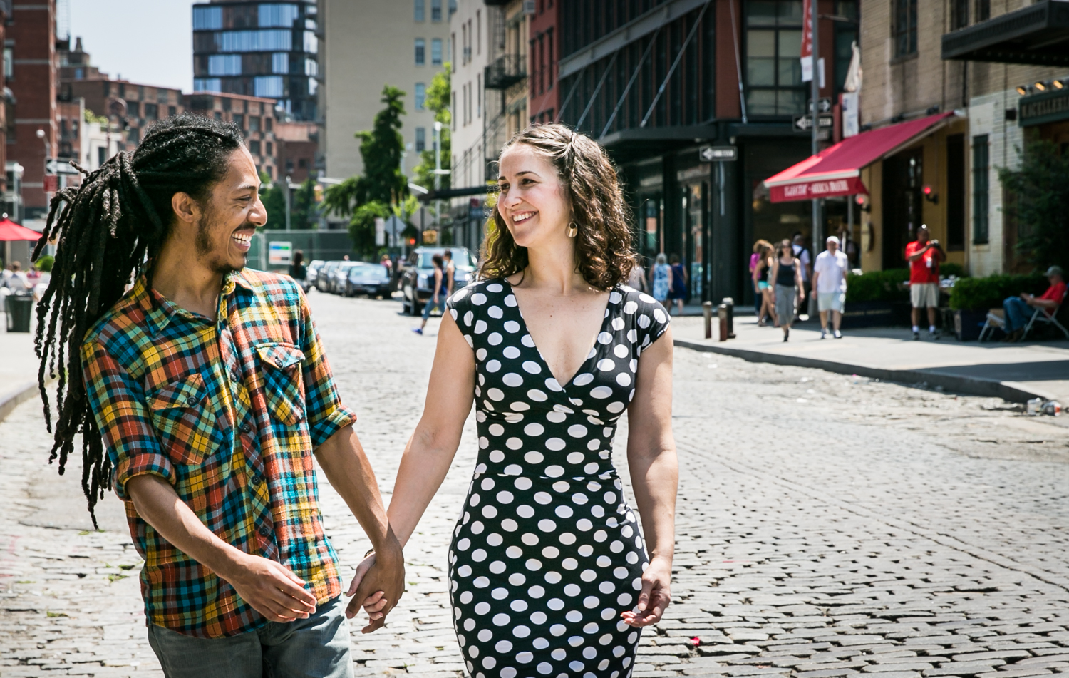 Couple walking hand-in-hand on cobblestone street