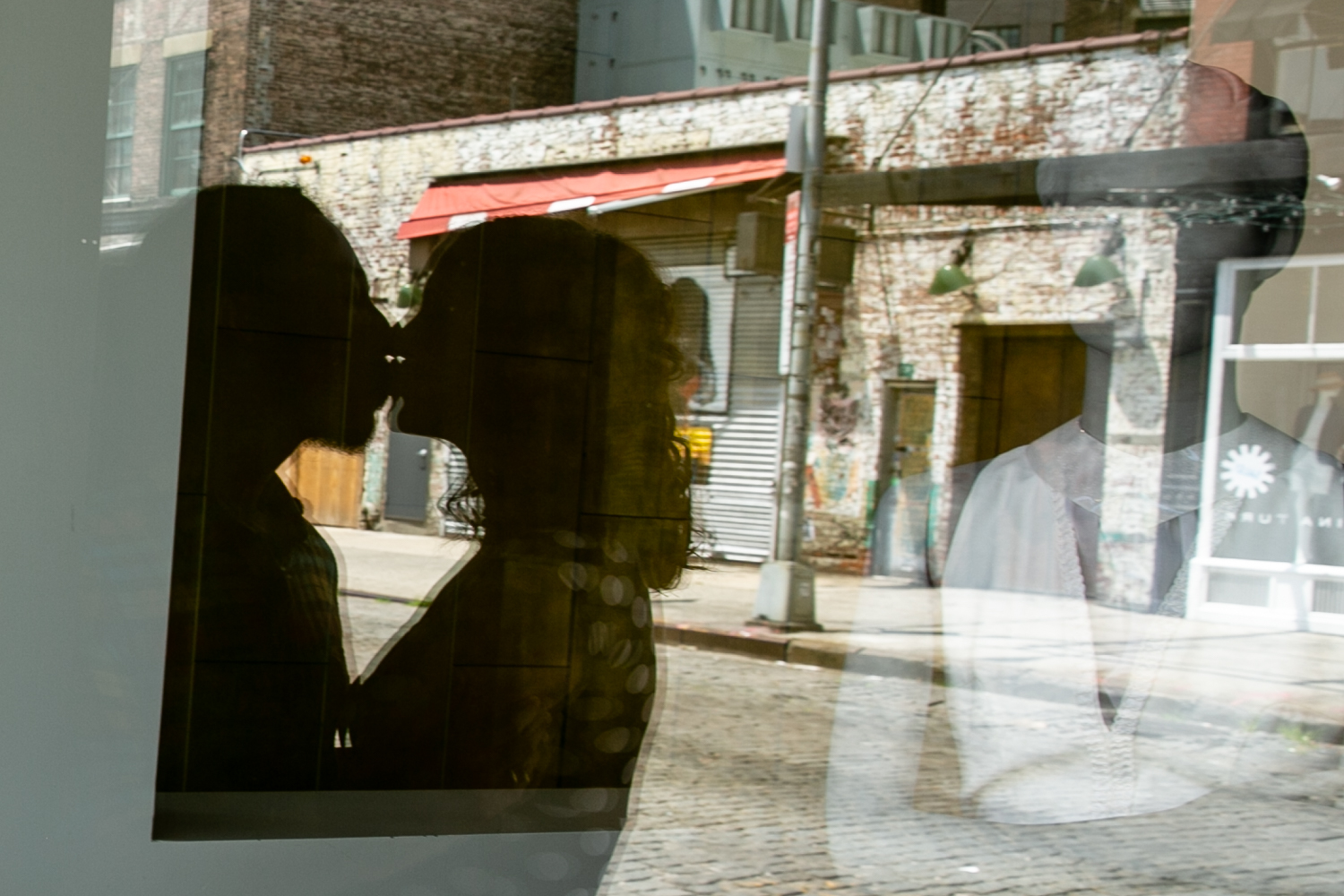 Reflection in window of couple kissing
