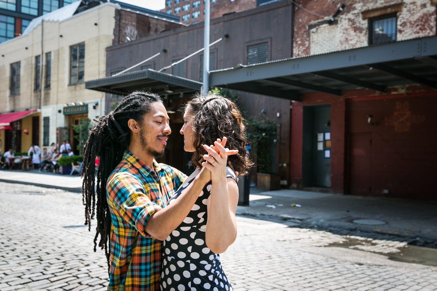 Meatpacking District engagement photos of couple dancing on cobblestone street