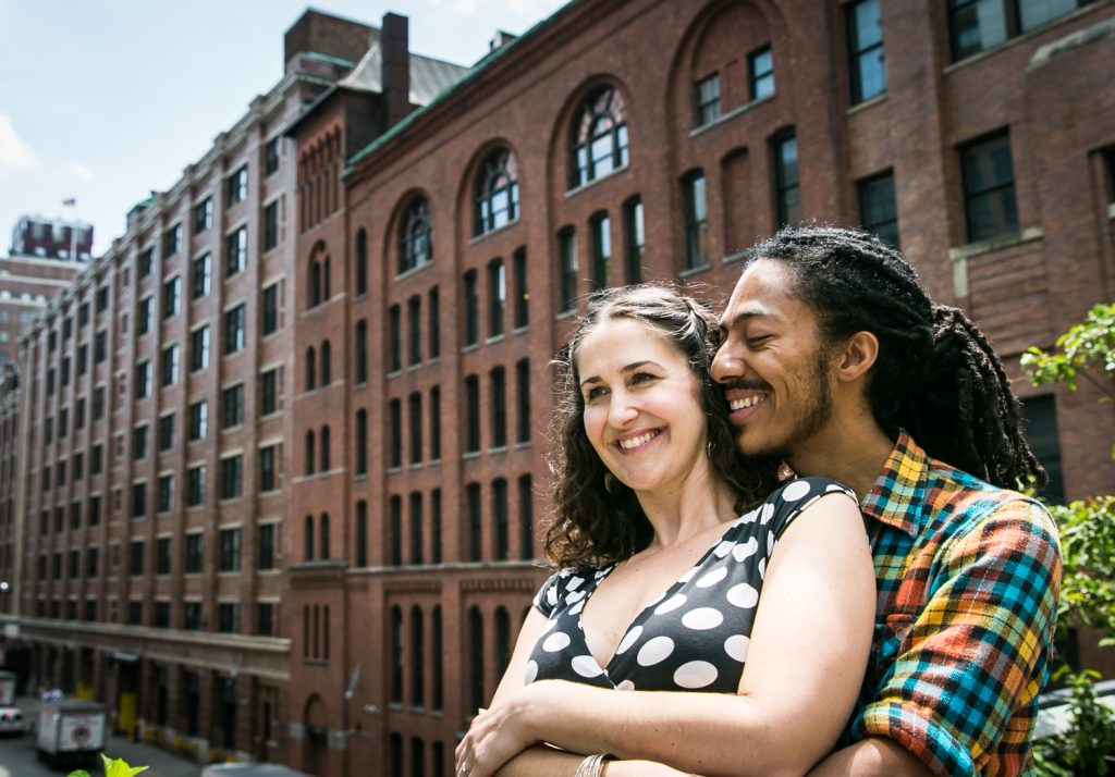Meatpacking District engagement photos of couple hugging in front of warehouse building