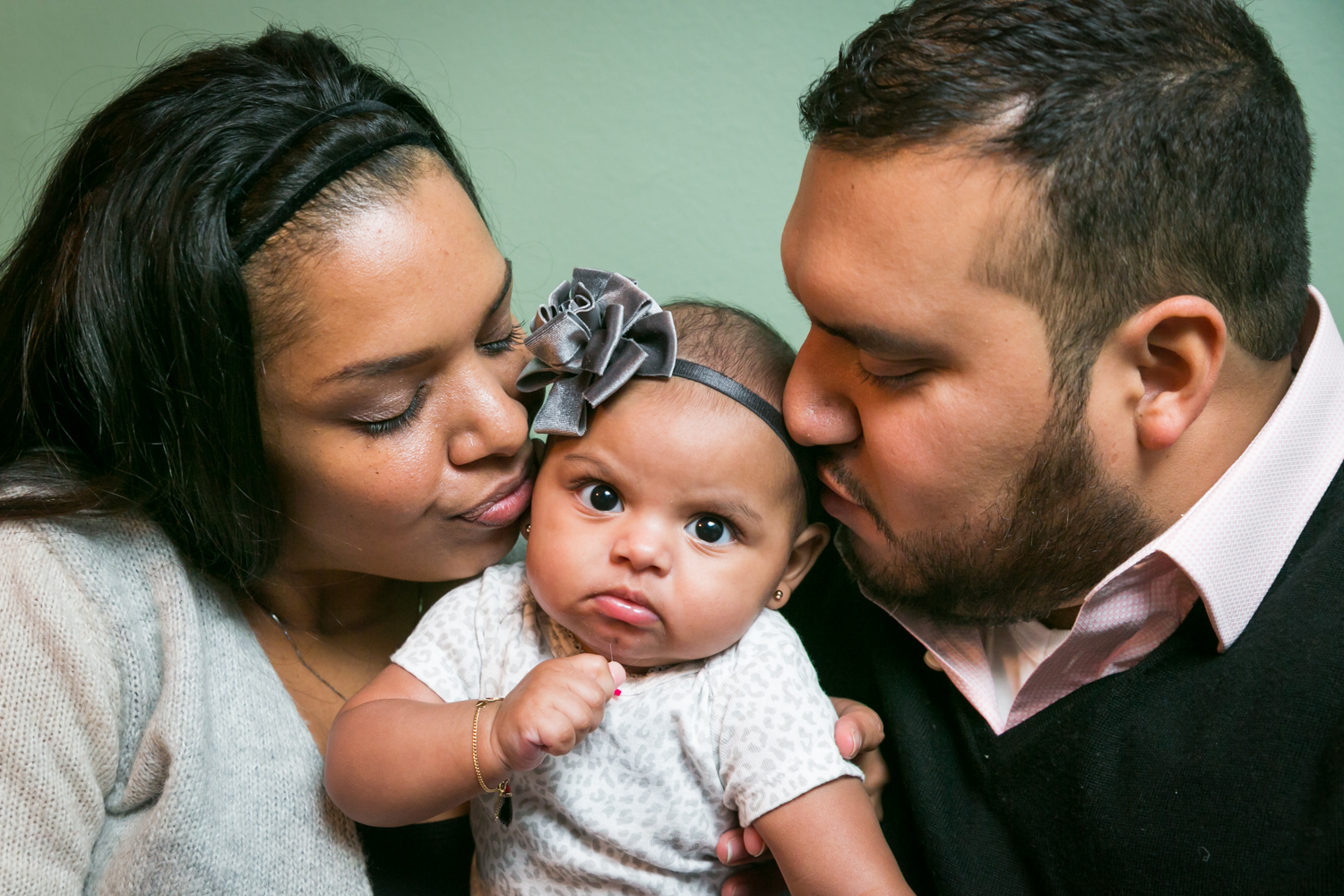 Prospect Park family portrait of parents kissing angry baby on both cheeks