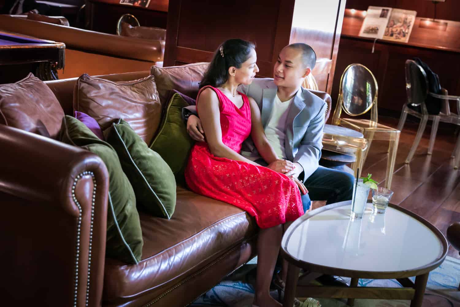 Couple sitting on couch at bar during a Hudson Hotel engagement shoot