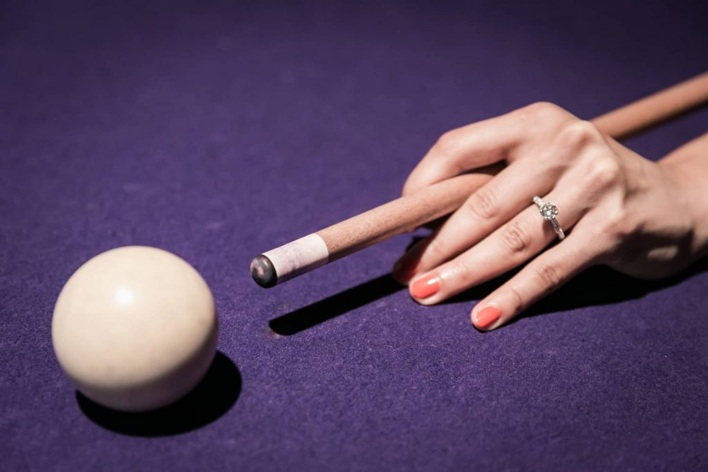 Close up on woman's hand about to hit cue ball during a Hudson Hotel engagement shoot