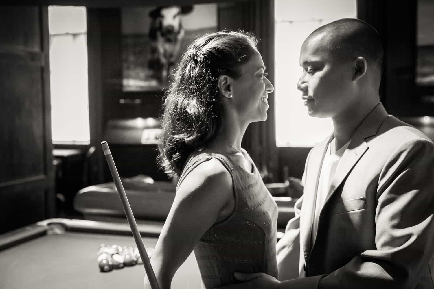 Black and white photo of couple leaning on pool table during a Hudson Hotel engagement shoot