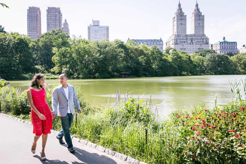 Couple walking beside Central Park lake