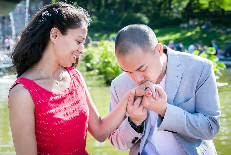 Man kissing woman's hand at Bethesda Fountain