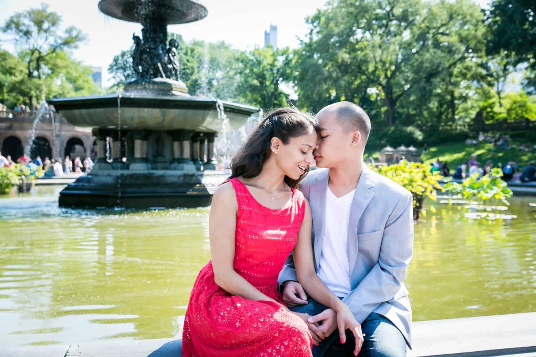 Man kissing woman beside Bethesda Fountain