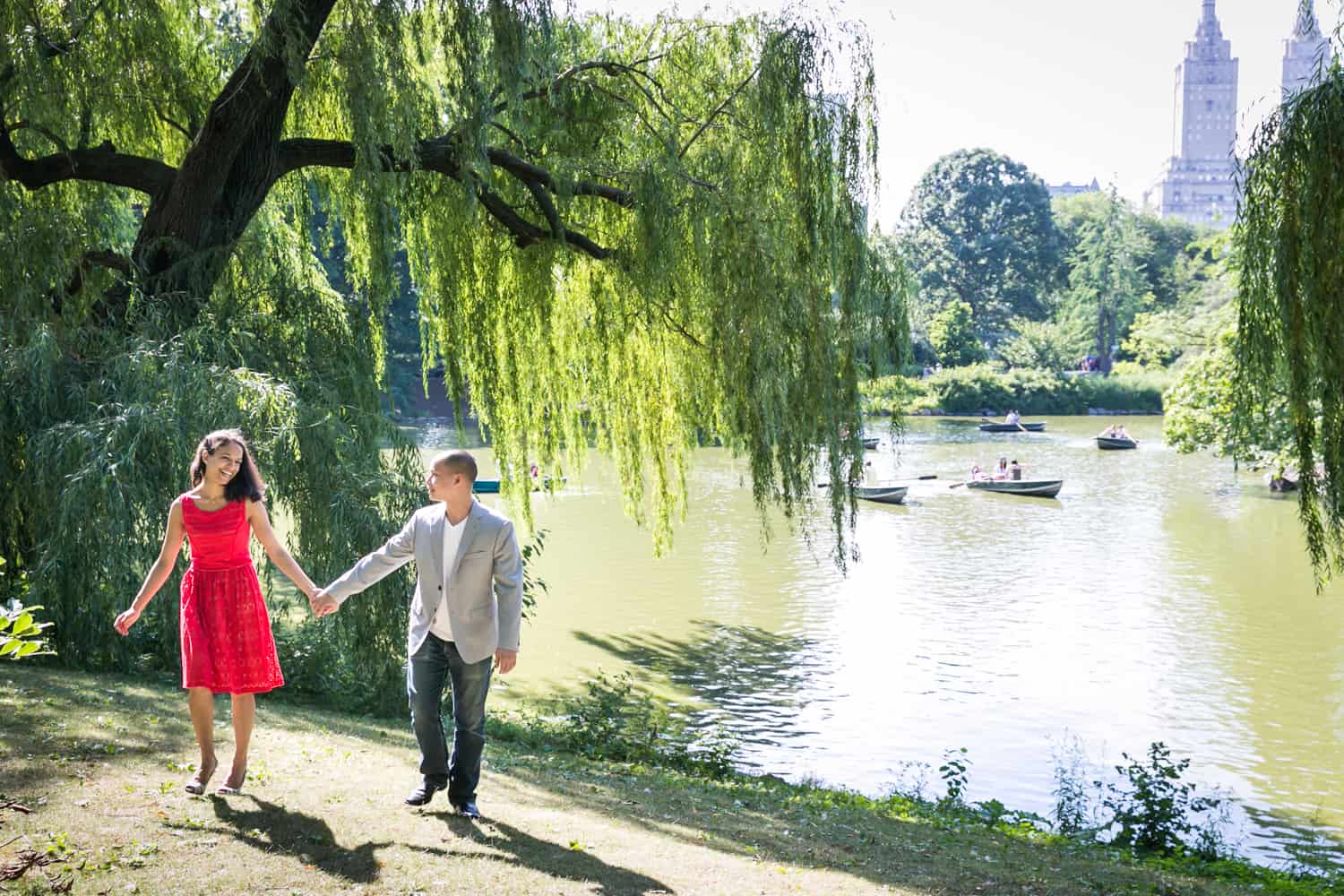 Couple walking beside Central Park lake