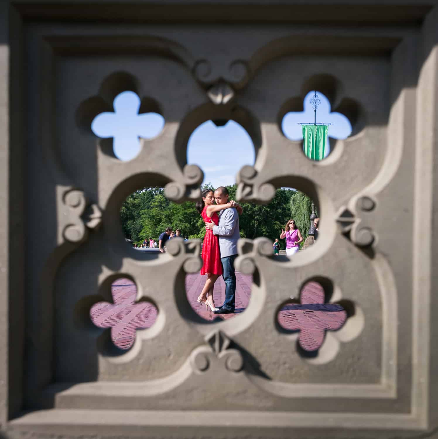 View through Bethesda Fountain fence of couple hugging