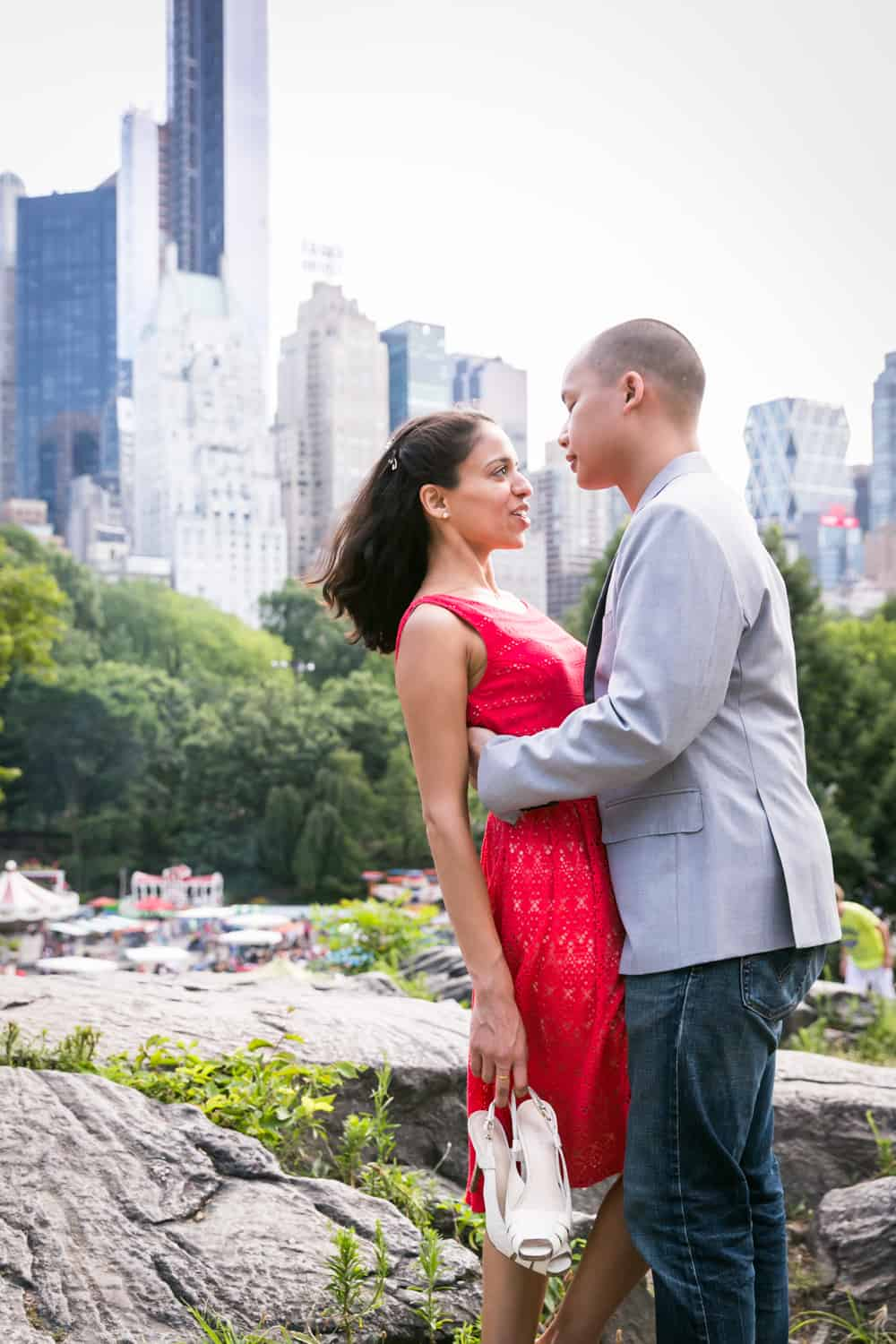 Couple on top of Umpire Hill in Central Park with NYC skyline in background