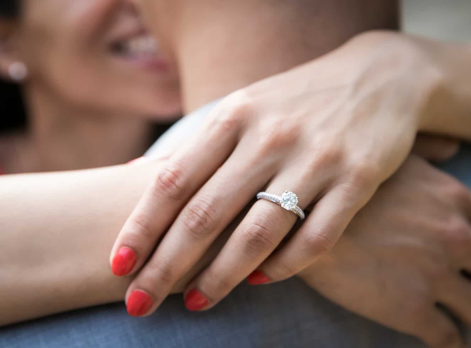 Close up of woman's hand wearing engagement ring
