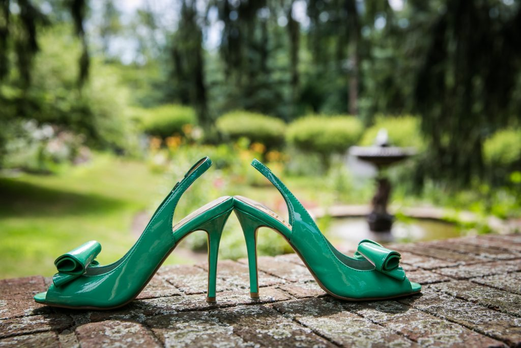 Green high heels on brick wall at a Round Hill House wedding