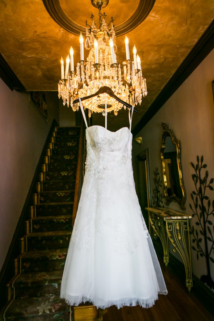 Wedding dress hanging from chandelier at a Round Hill House wedding